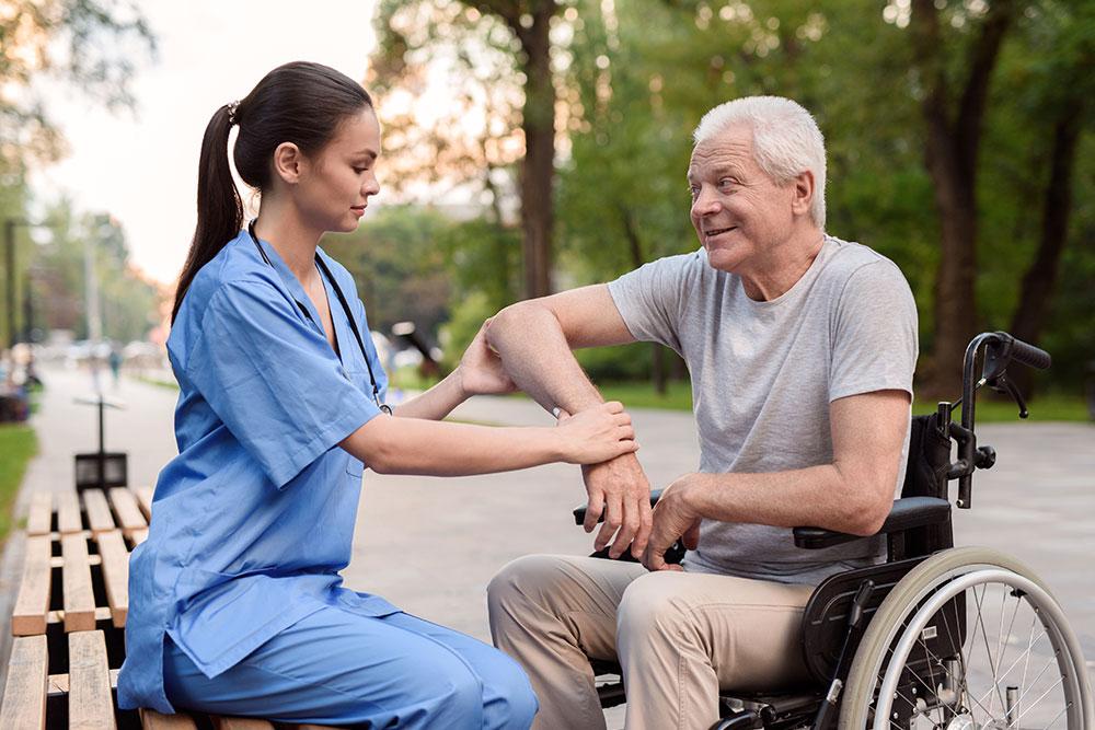 Female Nurse helping Patient in wheelchair